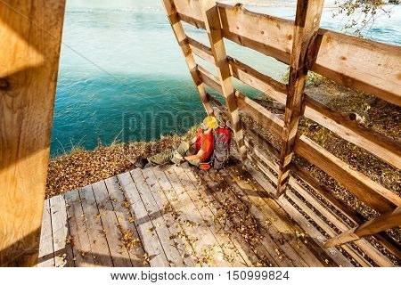 Young male with beard traveling, resting on the banks of mountain river sitting in hut of branches, with tourist rucksack while enjoying nature view and summer rest