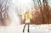 Winter landscape beautiful snowfall happy woman playing with falling snow. Asian girl having fun playfully throwing snow playing outside with arms up in the air playful on a sunny day in wintertime. poster