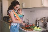 Young mom cooking in the kitchen with the baby. Vegetarian healthy food. Healthy food breastfeeding mothers. poster