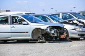 several cars in a scrap yard available for spare parts poster