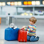 Cute little kid boy with blue and red suitcases and toy on international airport. Happy child wating for flight and going on vacations. poster