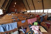 People's belongings are strewn across a church sanctuary after a natural disaster. poster