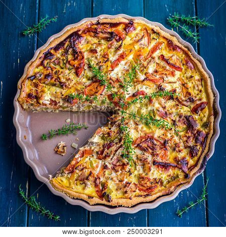 Quiche Provencal Decorated With Thyme On A Blue Table