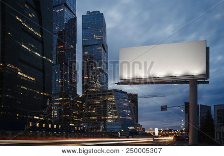 Blank Billboard At Night Time In The City Next To Skyscrapers And Road With Lights On The Frame. 3d