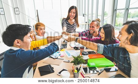 Multiethnic diverse group of office coworker or business partner fist bump in modern office. Colleague partnership teamwork, university student, congratulation event, job or mission accomplish concept poster