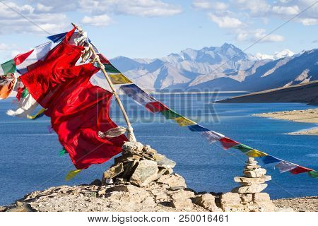 Buddhist Prayer Flags On The Wind Against The Blue High Altitude Tso Moriri Lake, Himalayas Mountain