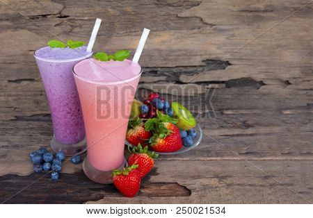 Strawberry and blueberry smoothies juice,beverage healthy fruit the taste yummy In glass drink episode morning on wood background. poster