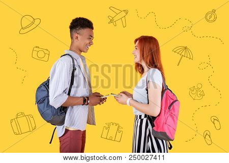 Planning Journey. Cheerful Young Friends Holding Modern Devices And Smiling To Each Other While Plan