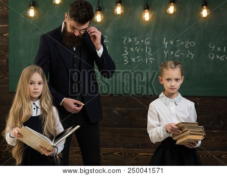 Education. Education Process At School Lesson, Teacher Gives Education To Little Girls. Improving Yo