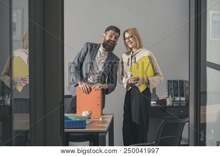 Happy Colleagues In Modern Office. Business Couple Smile Meeting In Office. Bearded Man And Sensual