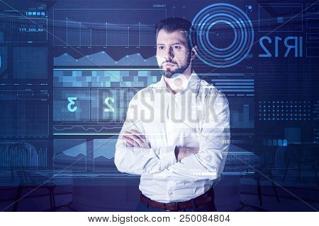 Calm Software Developer. Thoughtful Young Software Developer Standing With His Arms Crossed And Atte