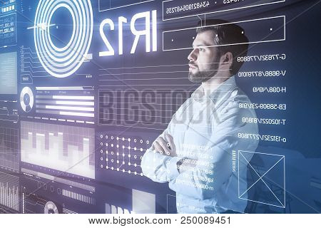 Careful Check. Attentive Reliable Web Developer Standing With His Arms Crossed And Checking The Info