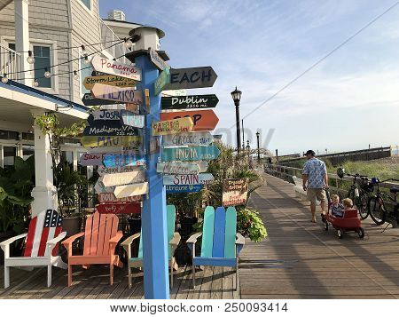 Bethany Beach, De: Directional Wayfinding Sign And Colorful Adirondack Chairs On The Boardwalk In Be