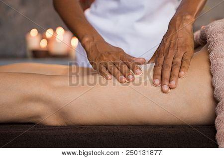 Closeup hands of beauty therapist massaging mature woman leg. Masseuse applying moisturizer on leg for anti-cellulite treatment at spa. Beautician hand doing massage with moisturiser.