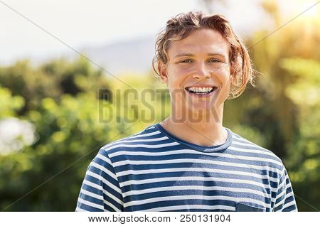 Cheerful smiling man with long blonde hair looking at camera. Happy young man relaxing at park in a summer day. Portrait of handsome guy in casual looking at camera with thoothy smile.