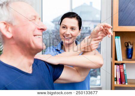Physio doing shoulder exercises with senior man