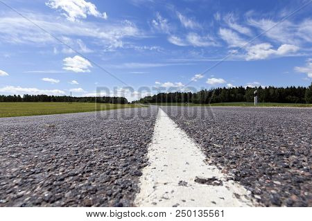 Long White Lines Dividing The Automobile Road Into Several Carriageways For Cars, A Summer Photo