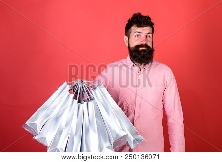 Hipster On Smiling Face Is Shopping Addicted Or Shopaholic. Guy Shopping On Sales Season With Discou