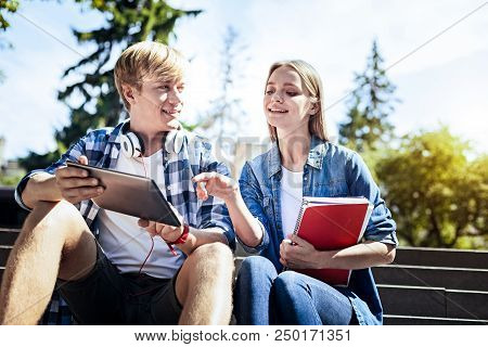 What Is That. Low Angle Shot Of Two Best Friends Sitting Outdoors And Smiling While Using Touchpad A