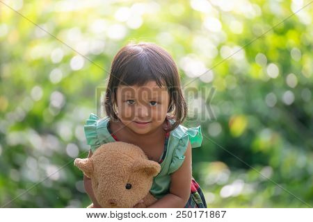 Asian Cute Little Girl (poor Kids) Playing In Garden,hugging Teddy Bear,smiling Face And Happy.teddy