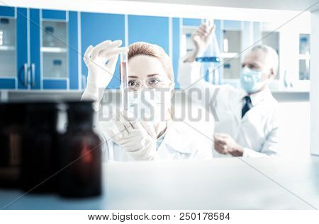 Laboratory Research. Serious Nice Female Researcher Wearing Protective Equipment And Holding A Test