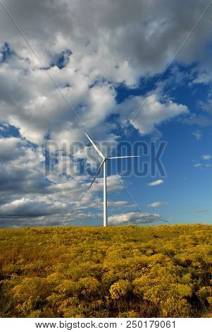 A Wind Turbine Just Over The Hill With Yellow Wildflowers And A Cloudy Sky.