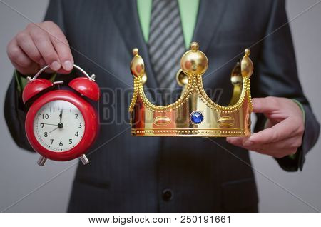 Businessman King Holding In Hands A Gold Crown And Red Alarm Clock. Winner Award Ceremony Time. Time