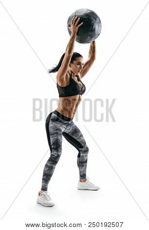 Strong Woman Doing Exercise With Med Ball. Photo Of Latin Woman In Fashionable Sportswear Isolated O