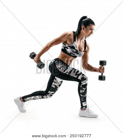 Sporty Woman Training Muscles Of Hands And Legs Using A Dumbbells. Photo Of Muscular Latin Woman In