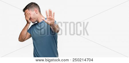 Handsome young casual man covering eyes with hands and doing stop gesture with sad and fear expression. Embarrassed and negative concept.
