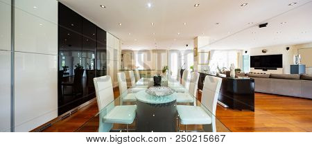Dining room with leather chairs, glass table and parquet. Nobody inside