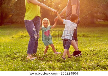 Family, Happiness, Childhood And People Concept - Happy Young Family Playing Game With Their Childre