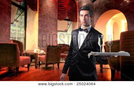 Handsome waiter serving wine glasses in a lounge bar