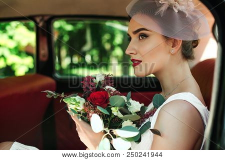 Beautiful Bride With Wedding Bouquet Sitting In Car. Trendy Bridal Bouquet. Perfect Bridal Makeup An