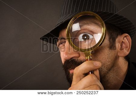 The Curious Detective Is Looking With Magnifier Or Magnifying Glass Or Loupe On Dark Gray Background
