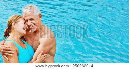 Zwei verliebte Senioren als Paar im Hotel Pool im Urlaub im Sommer