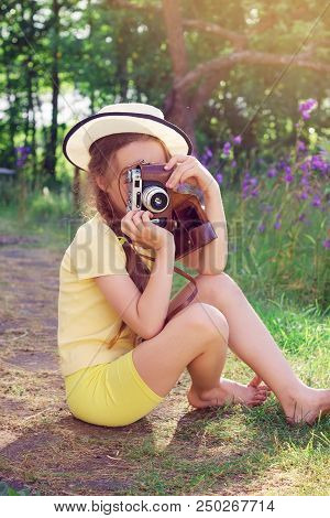 Toned Portrait Of Cute Little Girl In Retro Outfit Taking Pictures With Old Film Camera.