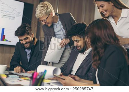 Group Of Business People Working In An Office, Executive Signing A Contract. Focus On The Man Signin