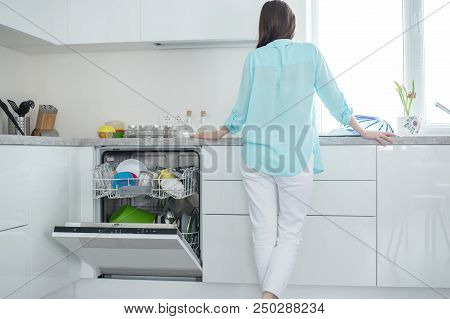 A woman in white jeans and a turquoise shirt stands with her back next to an open dishwasher in a white kitchen interior in front of the window. poster