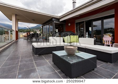 Large terrace furnished with outdoor furniture. Nobody inside
