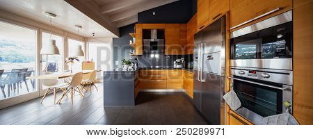 Front view modern wooden kitchen with table and chairs. Nobody inside