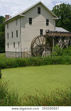 A White Gristmill Behind A Green Algae-covered Pond