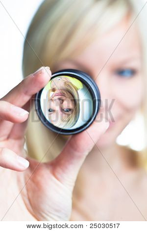 Optics concept: pretty young woman showing the principle of imaging through a lens (focus on the image through lens)