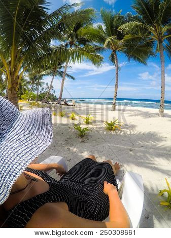 Over Shoulder Pov: Woman In Hat And Dress On Sun Lounger On Vacation At Idyllic Tropical Beach With