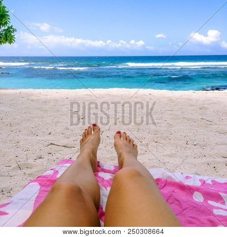 Legs And Feet With Fake Spray Tan And Painted Toenails On Sun Lounger On Tropical Beach With Pink To