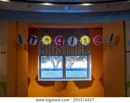 An Imagine Sign Hanging In Young Children S Playroom