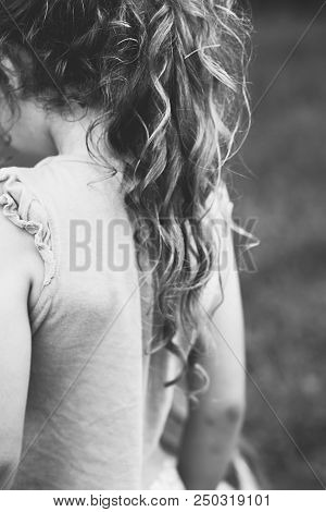 Black And White Portrait Of Little Girl Outside With Long Curly Hair, Back View. Soft Focused