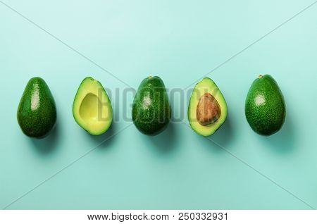 Organic Avocado With Seed, Avocado Halves And Whole Fruits On Blue Background. Top View. Pop Art Des