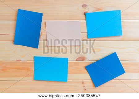 Bue And Pastel Colored Paper Cards On Wooden Background