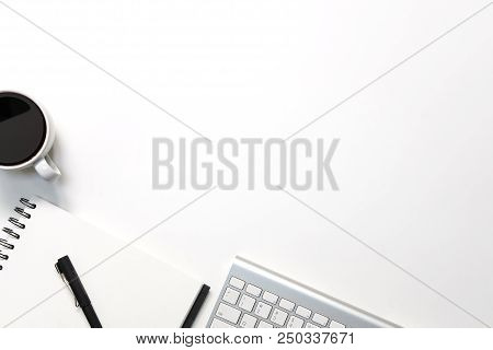 Modern White Office Desk Table With Keyboard Computer, Coffee, Pen And Notebook Paper With Workspace
